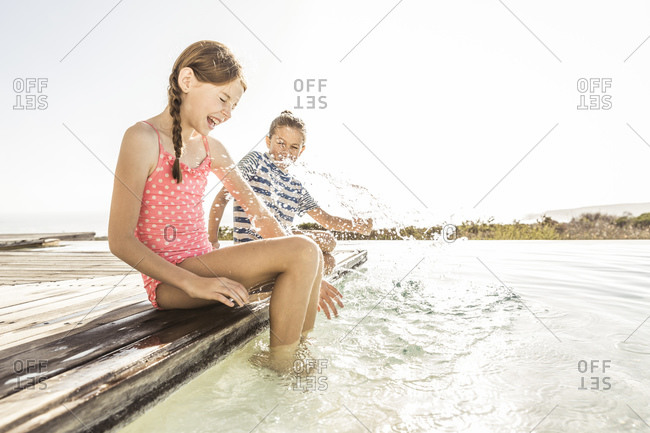 Two playful girls splashing with water at the poolside