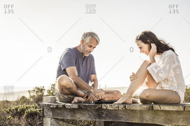 Couple sitting on boardwalk at the coast playing backgammon