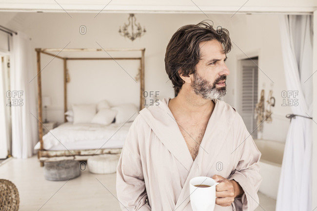 Man wearing bathrobe with a cup of coffee in bedroom