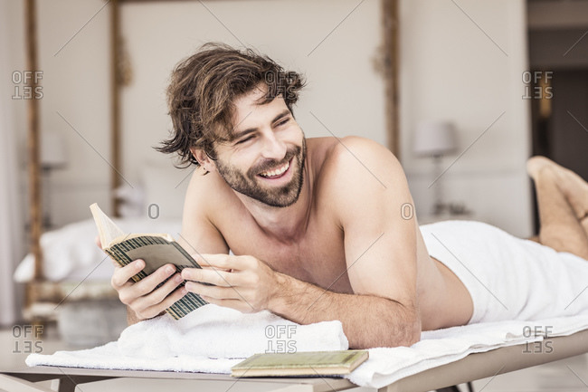 Young man with beard reading a book- lying on lounge