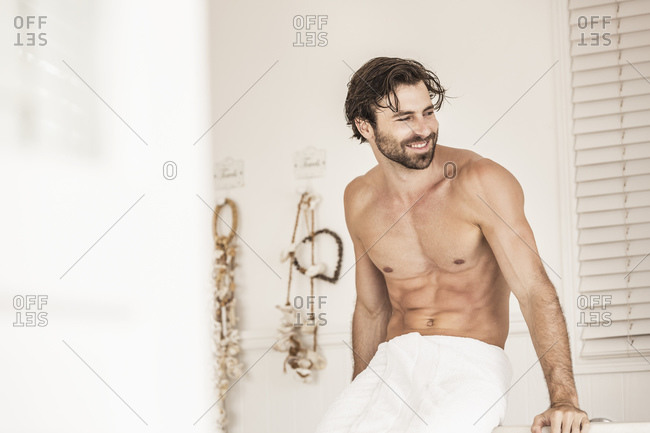 Shirtless young man in a bedroom