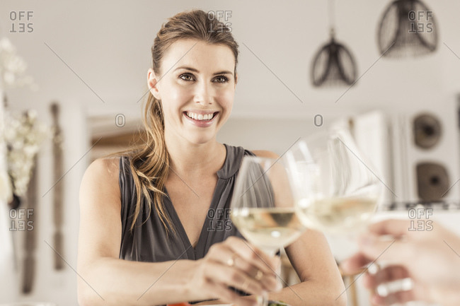 Portrait of smiling young woman having dinner with boyfriend clinking wine glasses