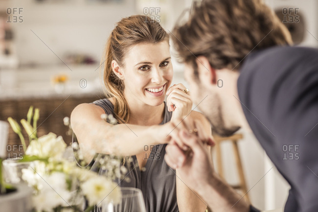 Smiling young woman looking at boyfriend kissing her hand