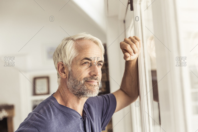 Portrait of mature man looking out of window