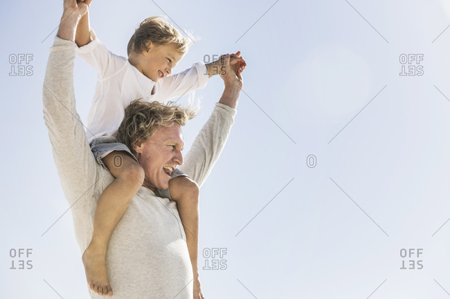 Father having fun with his son on the beach- carrying him piggyback