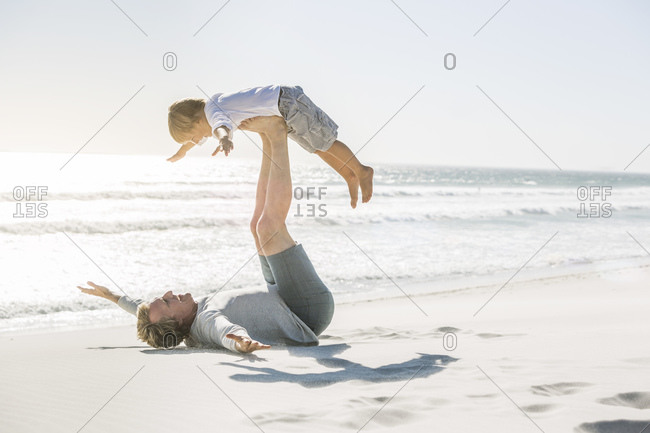 Father having fun with his son on the beach- pretending to fly