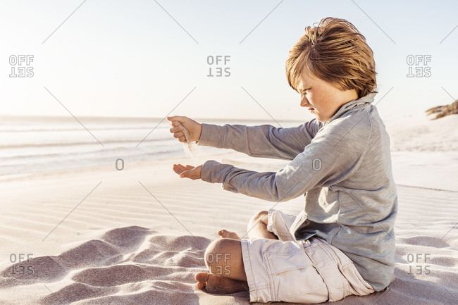 Little boy sitting on windy beach- watching sand trickling from his hands