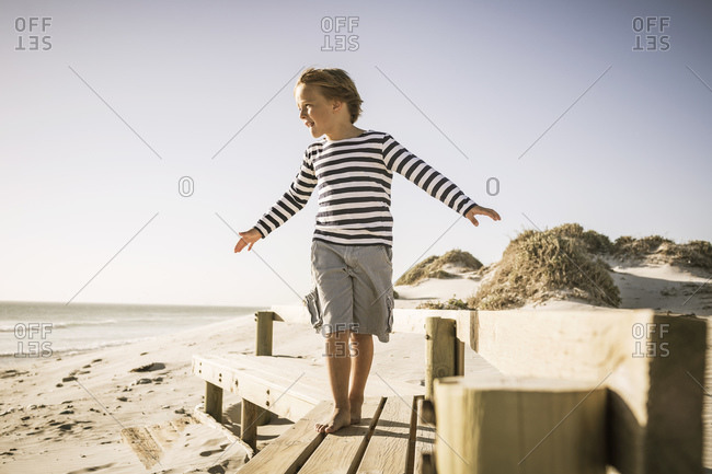 Boy balancing on boardwalk at the beach