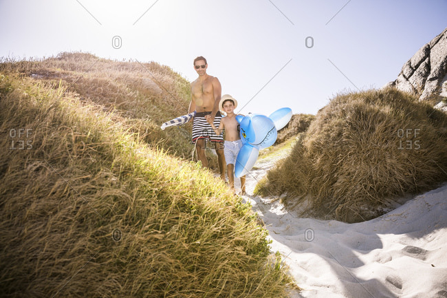 Father and son with inflatable shark walking through the dunes to the beach