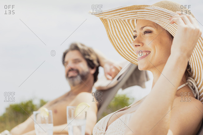 Couple relaxing on sun loungers