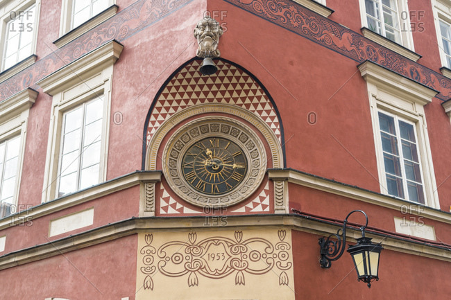 Ornamented historic clock at facade of a house at market square in the old town- Warsaw- Poland