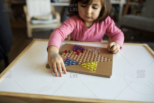 Little girl playing with marbles on table