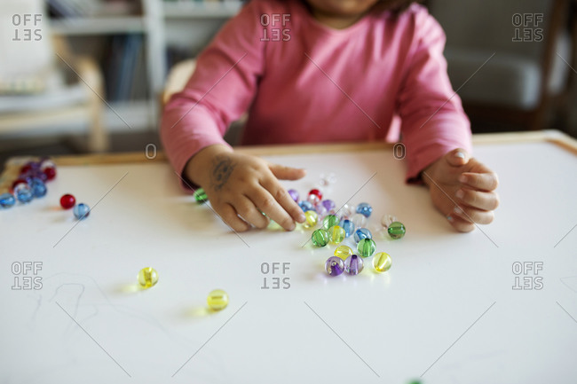 Crop view of girl playing with marbles on table