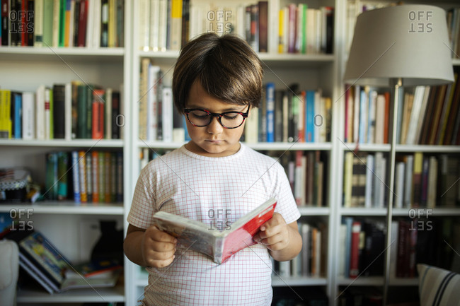 Portrait of serious boy with glasses standing in front of book shelves reading a comic