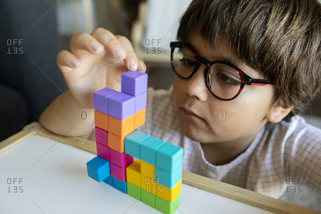 Portrait of little boy with glasses playing with building blocks