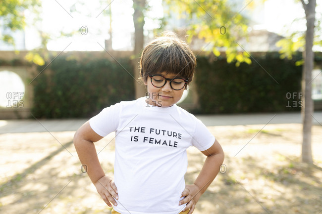 Proud little boy standing in the street with print on t-shirt- saying the future is female