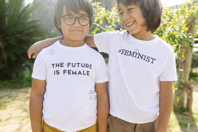 Two boys standing in the street with print on t-shirt- saying feminist and the future is female