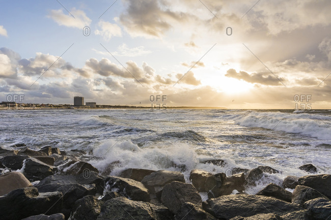 September 17, 2019: Germany- Mecklenburg-West Pomerania- Warnemunde- Sea waves crashing against rocks at sunset