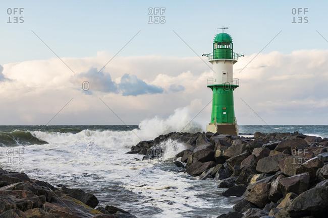 Germany- Mecklenburg-West Pomerania- Warnemunde- Lighthouse and sea waves crashing against rocks