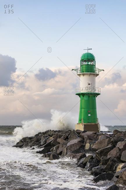 Germany- Mecklenburg-West Pomerania- Warnemunde- Lighthouse and sea waves crashing against rocks at sunset