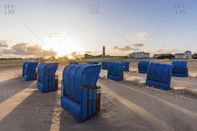Germany- Mecklenburg-West Pomerania- Warnemunde- Hooded beach chairs on beach at sunset