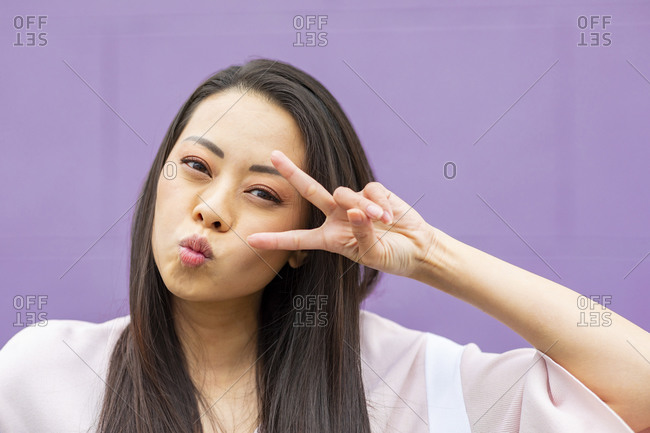 Portrait of woman pulling funny faces against purple background