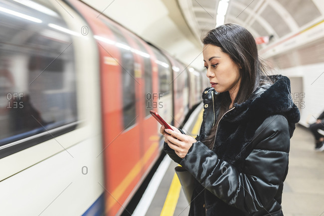 Portrait of woman waiting at underground station platform looking at smartphone- London- UK