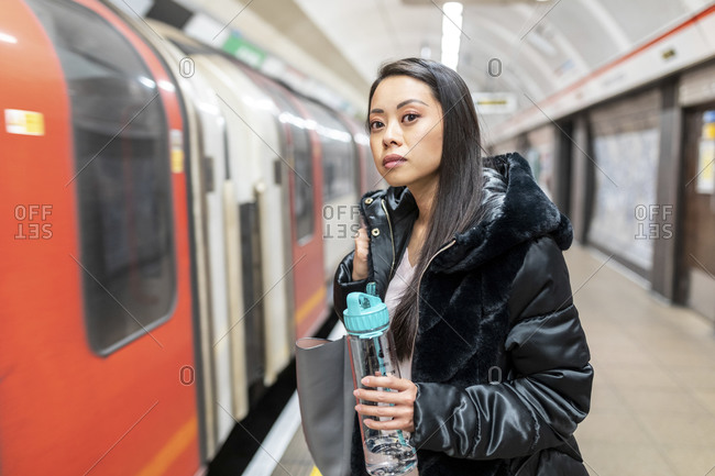 Portrait of woman with drinking bottle waiting at underground station platform- London- UK