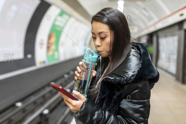 Portrait of woman with drinking bottle and cell phone at underground station platform- London- UK