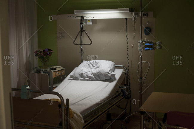 Empty hospital bed at night
