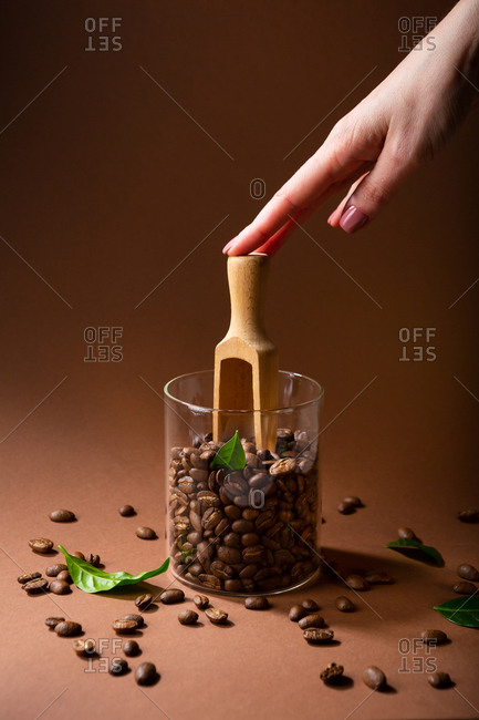Hand holding wooden spoon in jar of coffee beans
