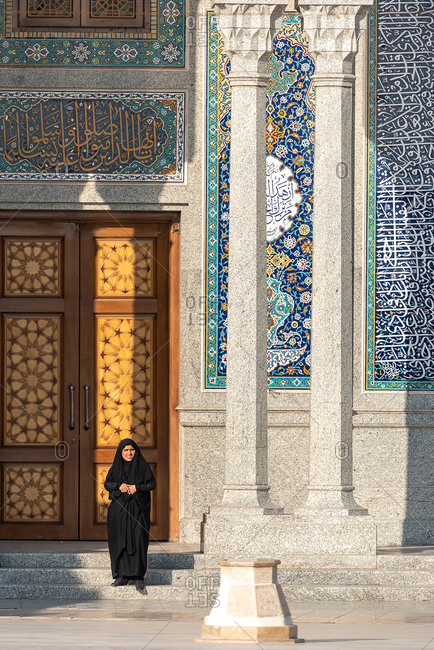 February 28, 2019: Iranian woman in front of Hassan Mosque in Qom, Iran