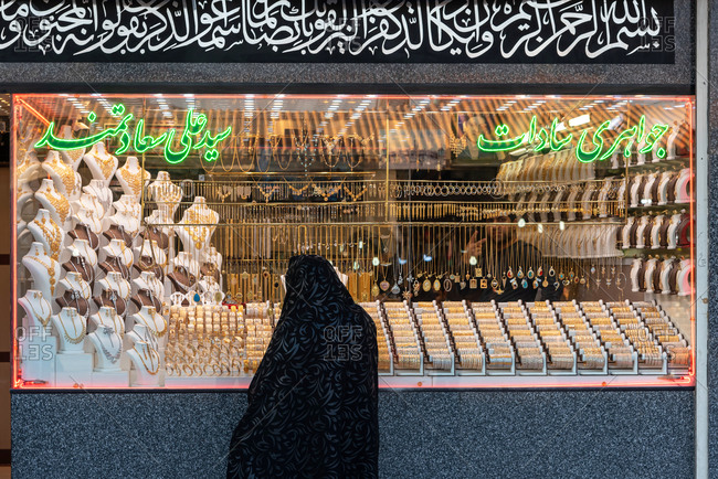 February 28, 2019: Iranian woman dressed in black in front of a jewelry shop. Qom, Iran