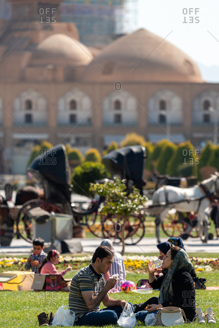March 2, 2019: Iranian people resting and having a picnic on the grass at Naghsh-e Jahan Square. Isfahan, Iran