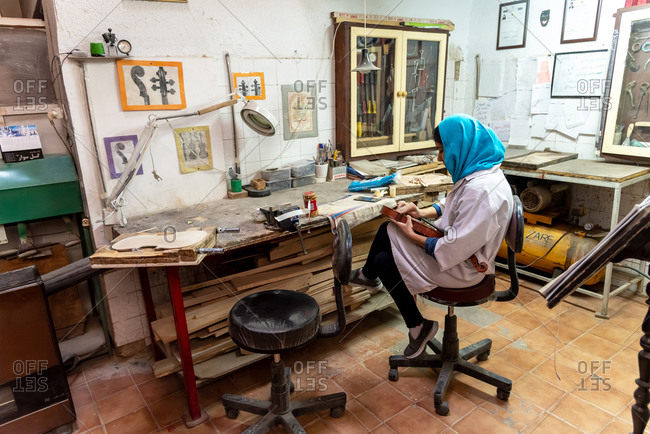 March 5, 2019: A luthier working on a violin in her workshop in Yazd, Iran
