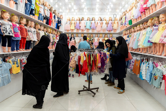 March 6, 2019: Muslim women dressed in black choose kids clothes. Isfahan, Iran