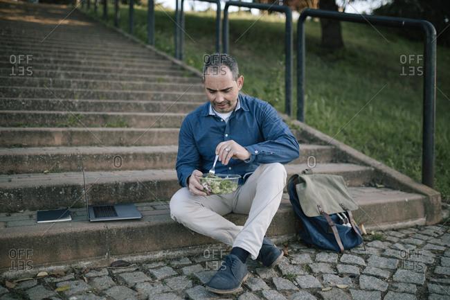 Man eating a salad outdoors