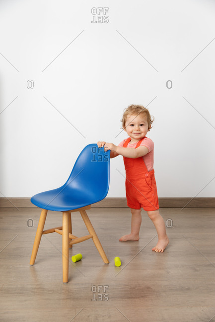 Cute baby standing next to blue chair