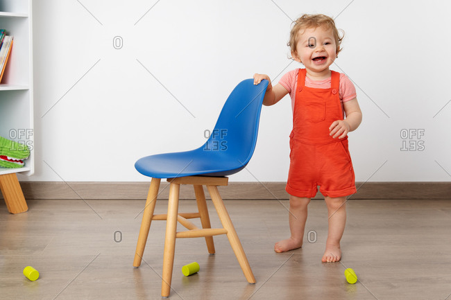 Laughing baby standing next to blue chair in playroom