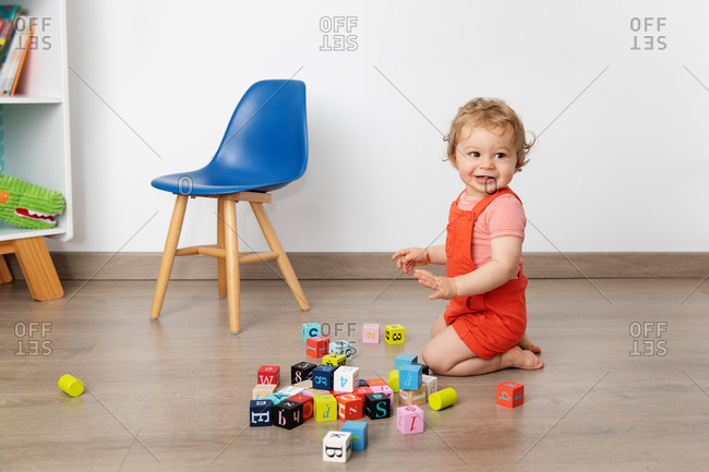 Smiling baby playing with alphabet blocks