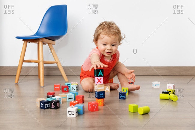 Cute baby piling up blocks in playroom