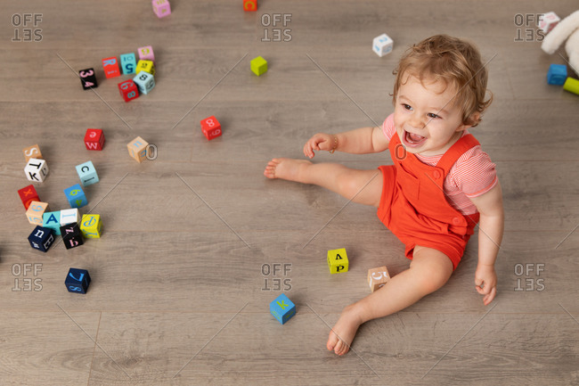 Laughing baby sitting on floor playing with alphabet blocks
