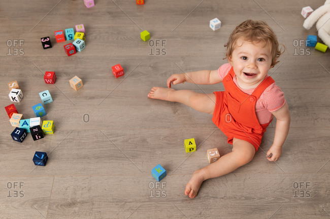 Smiling baby sitting on floor playing with alphabet blocks