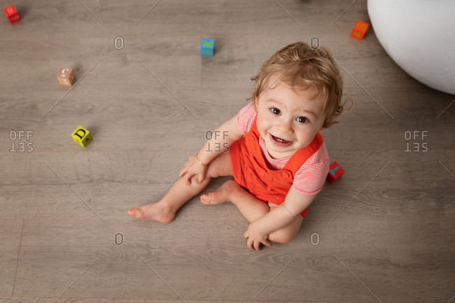 Cute baby sitting on floor playing with alphabet blocks