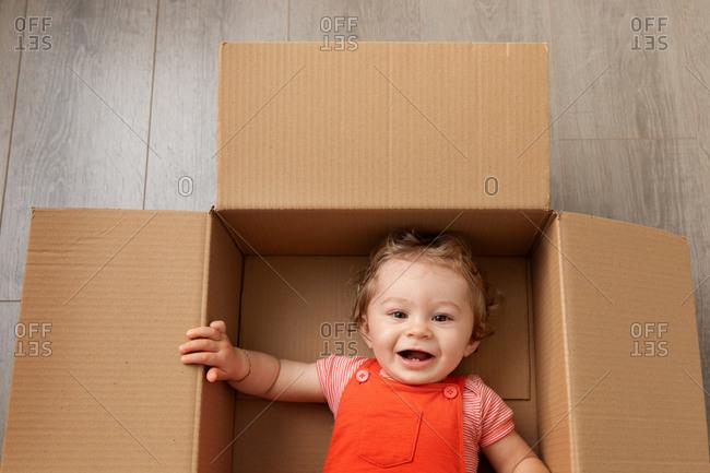 Cute baby lying in a cardboard box