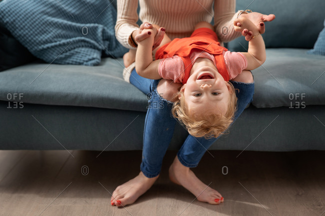 Happy baby playing on mother's lap with head upside down