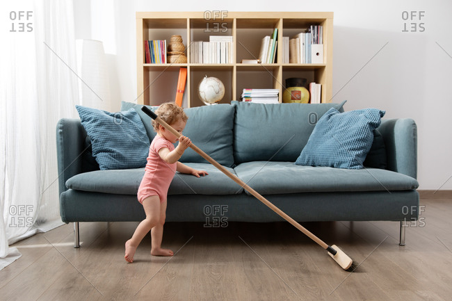 Young toddler sweeping living room floor with broom