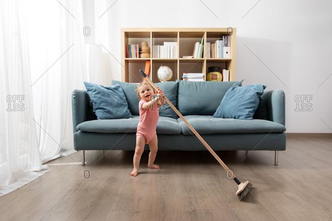 Happy baby sweeping living room floor with broom