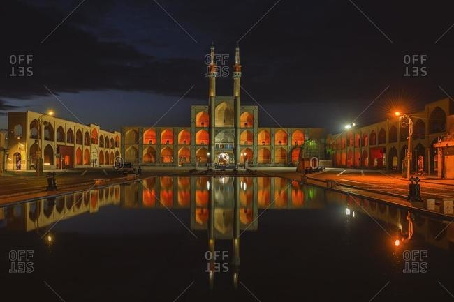 March 5, 2020: Amir Chaqmaq complex facade illuminated at sunrise and reflecting in a pond, Yzad, Yazd province, Iran, Asia
