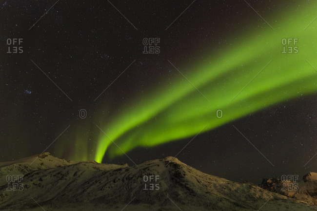 Northern Lights over snow covered mountains, near Tromso, Norway, Europe